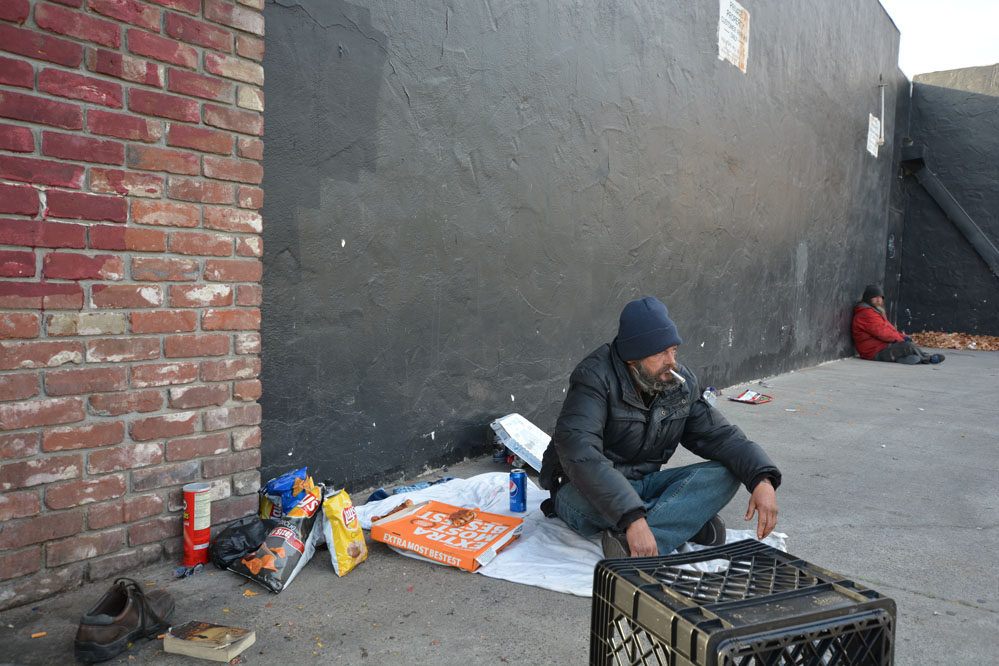 Homeless man sitting near wall