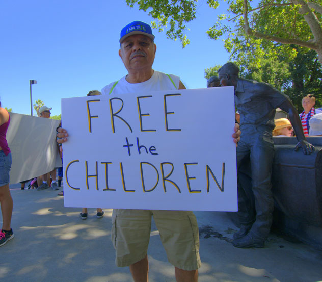 Johnny Hernandez holding sigh:  Free the Children
