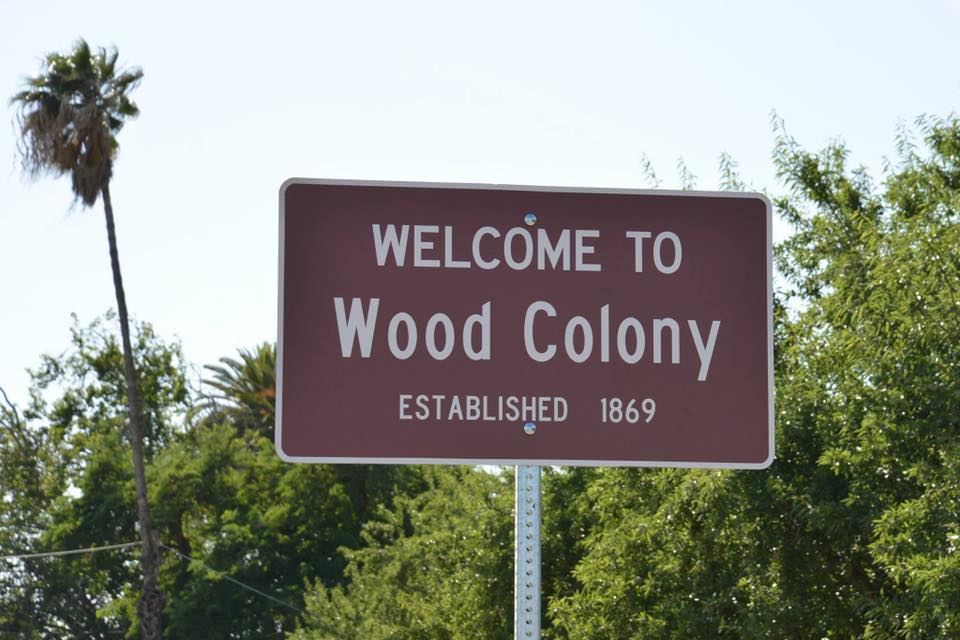 "Street sign: ""Welcome to Wood Colony"""